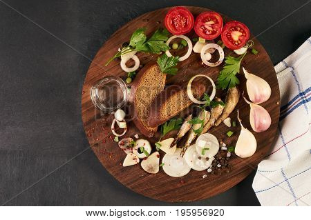 Cold glass of vodka with various traditional russian snack on wooden board over black stone background with copy space. Top view. The concept of national cuisine.