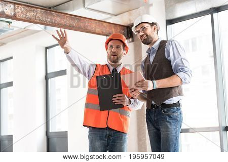 It will be luxurious apartment. Low angle happy constructor gesticulating hands while speaking with cheerful ganger