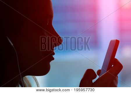 Silhouette of young girl with a phone sitting in the train and listening music - Face of a women typing a message on the smartphone during a travel - Main focus on the lips with marsala halo flare