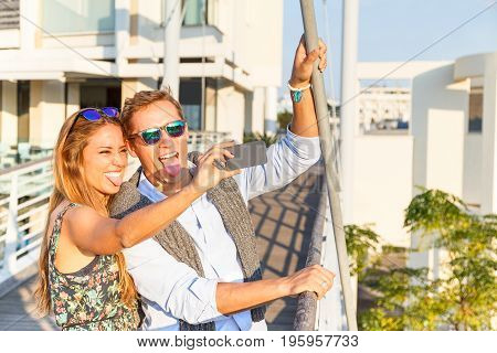 Young couple of best friends standing on the bridge and making funny faces for selfie portrait. Happy people smiling to the phone with hilarious facial expression. Concept of friendship and wandering.