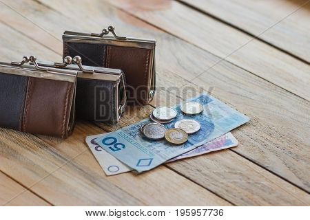 Polish Zloty With A Little Wallet On The Old Wooden Background
