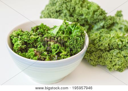 Kale salad in blue bowl and fresh kale leaves on white table. Kale chips mixed with fresh leaves. Vegetarian food. Healthy eating