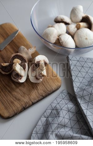 Fresh sliced mushrooms at wooden cutting board. Chopping food ingredients. Food background of fresh champignons at the old cutting board with copy space