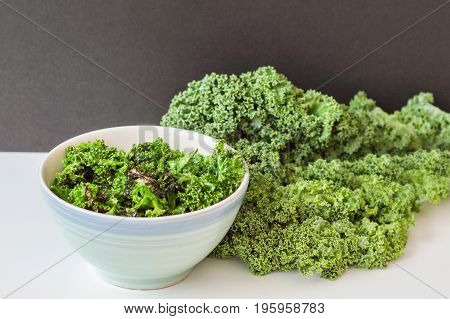 Bowl with crispy kale chips and fresh kale bunch on white table. Kale salad