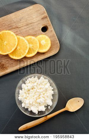 Cottage cheese with orange on cutting board with wooden spoon.