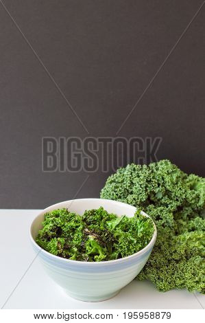 Vertical photo kale chips and fresh kale leaves on white table black board as background. Kale salad