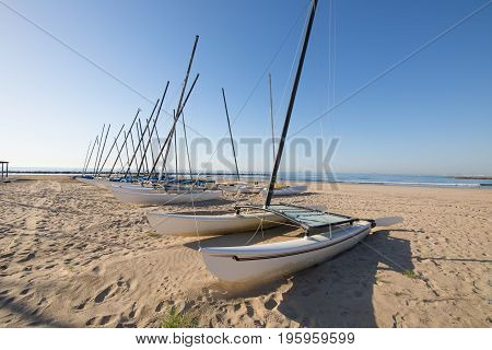 group of catamaran boats in row on the beach Els Terrers in Benicassim Castellon Valencia Spain Europe. Blue clear sky and Mediterranean Sea