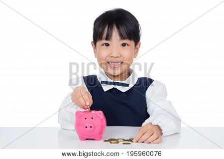 Asian Chinese Little Girl Putting Coins Into Piggy Bank