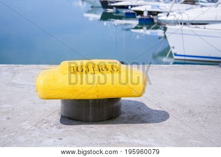 Mooring bollard on a pier with docked yacht on the background