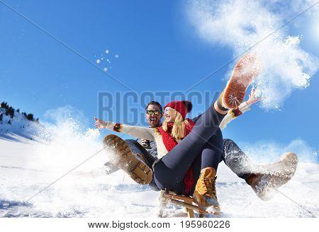 Young Couple Sledding And Enjoying On Sunny Winter Day.