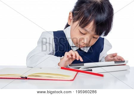 Asian Chinese Little Girl In Uniform Studying With Tablet Computer