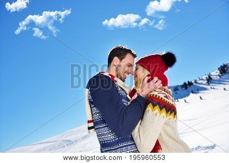 Loving couple embracing in winter park. They put colored caps and scarves
