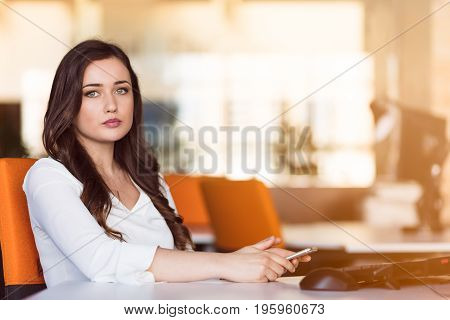 Happy pensive businesswoman planning and looking sideways at office.