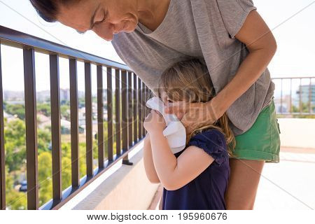 woman mother with grey shirt blowing nose of three years old blonde child with blue dress looking surprised expression at terrace of house with city and mountain views