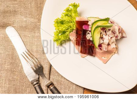 Danish specialties and national dishes high-quality open sandwich. Sandwich with pork roll sausage rullepoelse jelly and raw red onions served on a plate ready for eating