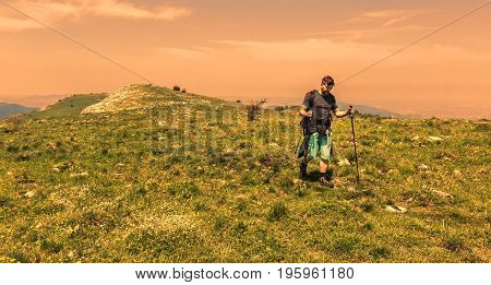 Young man with nordic sticks hiking at the dusk in Apuseni Mountains in TransylvaniaRomania.