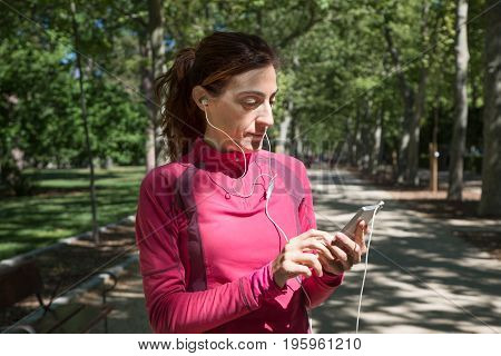 Runner Woman Using Mobile With Ear Headphones