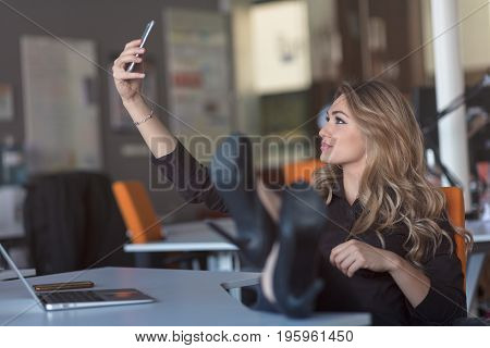 Beautiful young woman is making selfie in her workplace. She is relaxing and putting her legs on the table