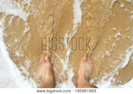 Top view of a man's leg standing on the sand and lapped by the ocean waves