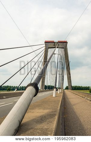 Closeup of the cable of a cable-stayed bridge over the river Bergsche Maas near the village of Heusden in North Brabant Netherlands. It is a cloudy day in the summer season.