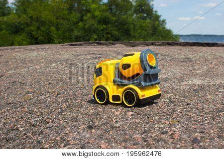 Toy car mixer on the dark asphalt with the rear