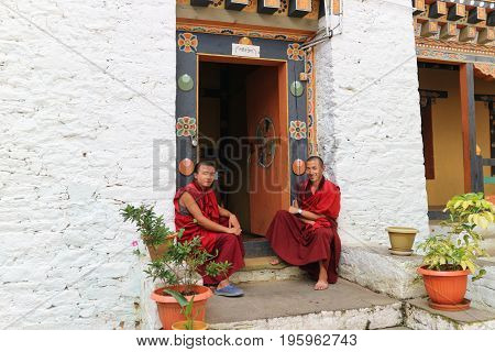 Thimphu Bhutan - September 15 2016: Two smiling young monks sitting in front of the door in Simtokha Dzong Thimphu Bhutan South Asia