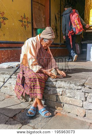 Thimphu, Bhutan - September 16, 2016: Old Bhutanese Woman Sitting In Front Of Her House And Cracking
