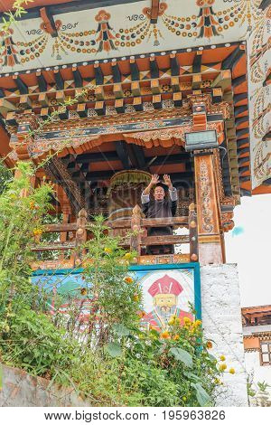 Thimphu Bhutan - September 15 2016: Low angle view of a smiling monk saluting in front of the prayer wheel in Simtokha Dzong Thimphu Bhutan South Asia