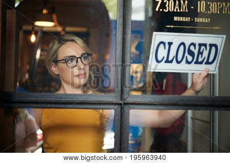 Pretty clothing store owner closing her shop
