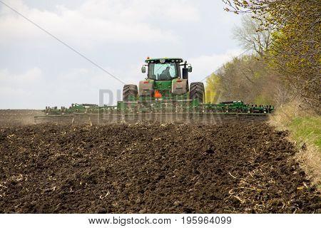 Kirovograd region Ukraine - April 17 2017: Farmer on tractor handles field on spring