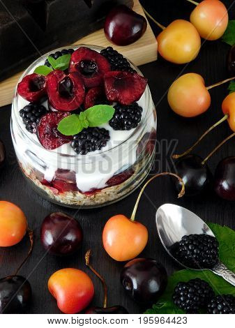 Oatmeal with yogurt and berries in a jar surrounded by cherries on a dark background. Layered breakfast