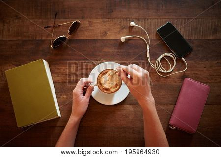 Hands of woman mixing sugar in her cappuccino, her belongings are around