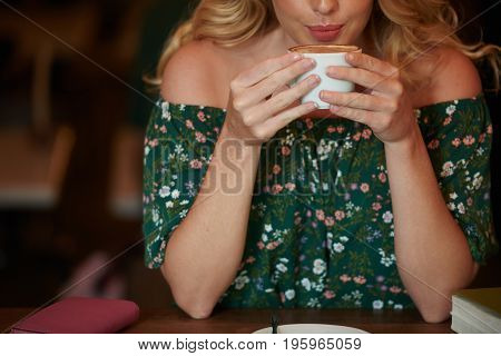Cropped image of smiling woman enjoying cup of coffee
