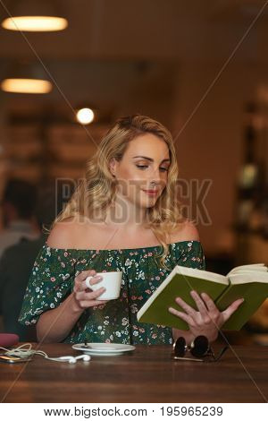 Pretty blond woman sitting in cafe with coffee and thick book