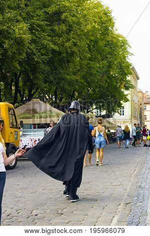 Lvov, Ukraine - 06.08.2016: Darth Vader on city street. Actor in costume Darth Vader walking. Dark Lord among us