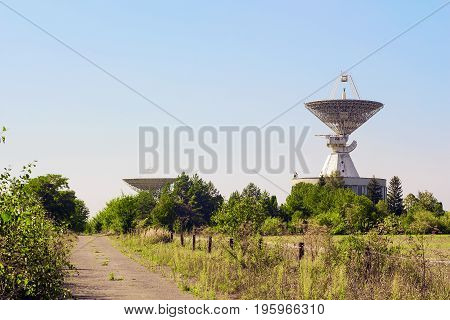Large satellite dish radar antenna station in field against blue sky. Space Communication Center