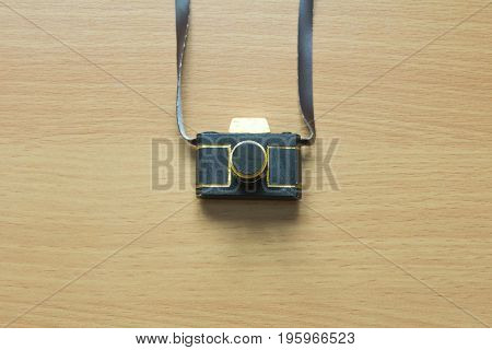 Black and gold color camera toy model on wood background