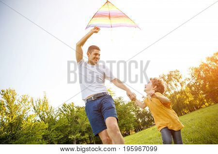 Happy man with little son in park running to set kite in air.