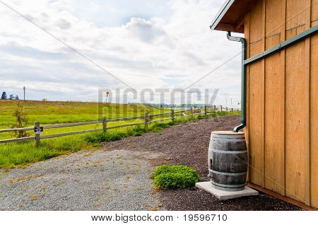 Gutters direct rainwater into a wooden rain barrel on the side of a building. Rural setting off freeway. Horiztal. Copy space. poster
