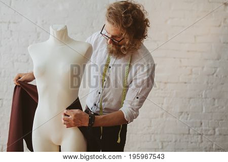 Stylish dressmaker using mannequin to create new clothing while working in parlour. poster