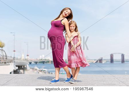 Happy family, pregnant mother and her daughter little girl child walking and hugging on the embankment in the summer day