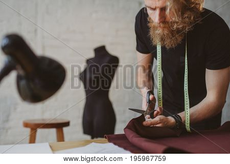 Blonde bearded man wearing black t-shirt tape measure cutting crimson fabric with scissors leaning on table.