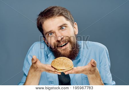 Young guy with a beard on a gray background holds a hamburger.