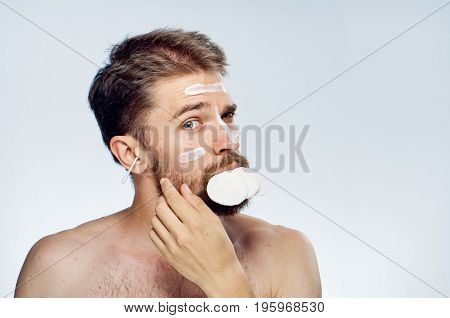 Young guy with a beard on a white isolated background, cotton pads, cosmetic cream.