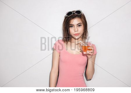 Beautiful young girl model stands on white background in sexy bathing suit with wet hair drinking orange juice