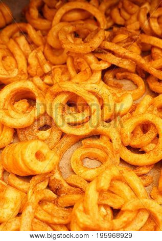 Crispy baked curly fries on a baking sheet