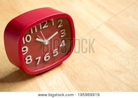 Red analog clock on wooden table background