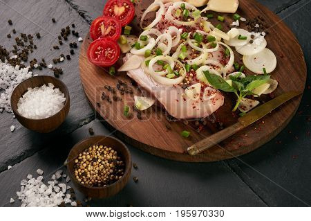 Raw food grocery full of proteins on wooden brown cutting rustic board on black stone background. Chicken fillet onion herbs. Healthy sport diet background. Healthcare lifestyle or proteins concept