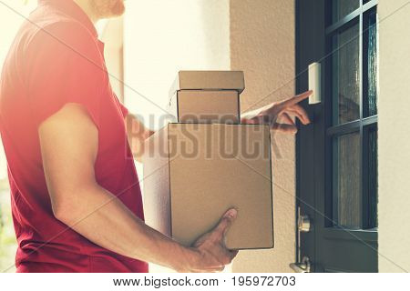 delivery service courier ringing the house doorbell with boxes in hands