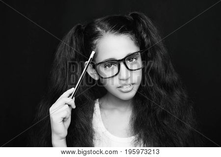 A Beautiful African Kid Girl In Glasses Holding Pencil In Hand